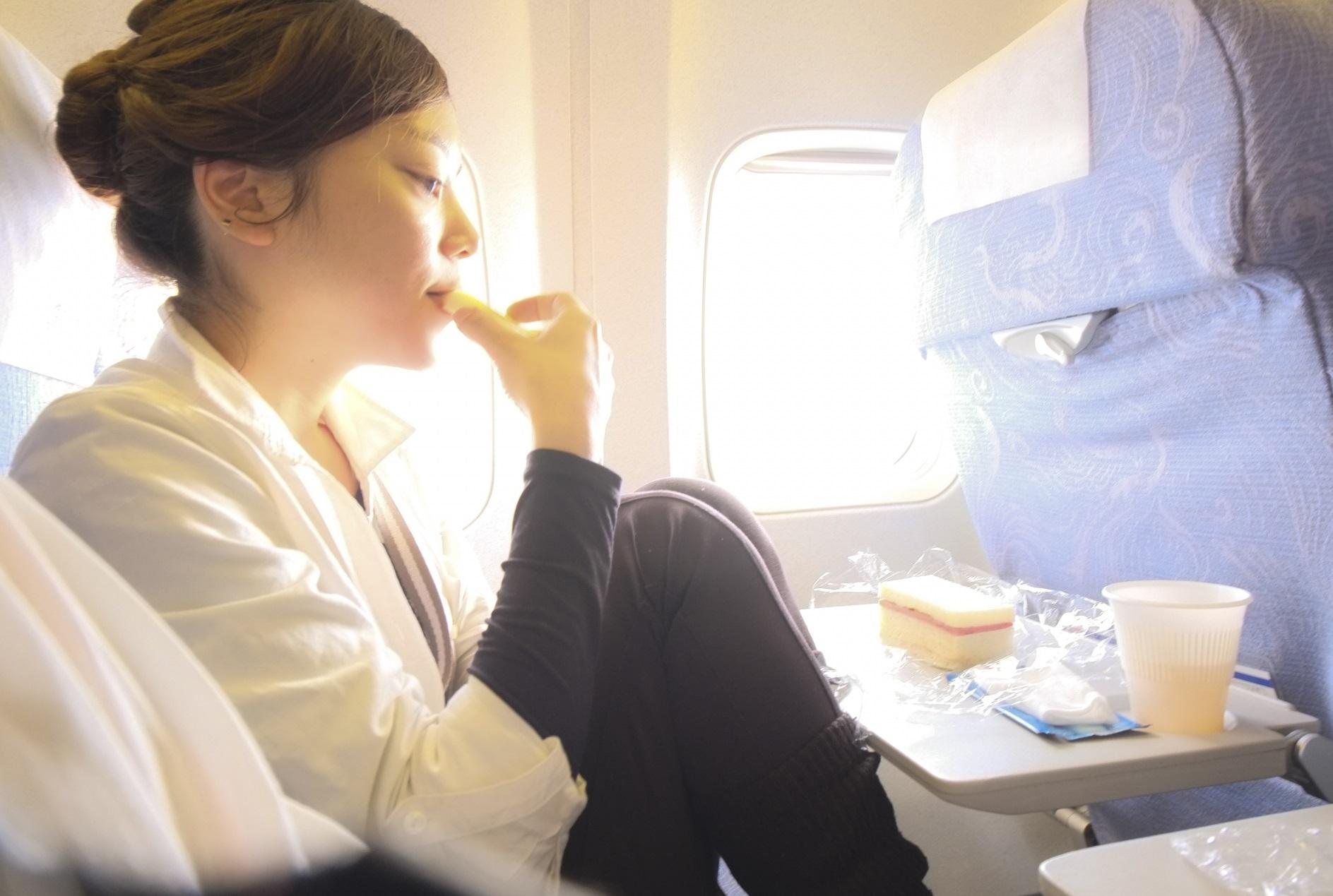 飛行機フライト_機内サービス_機内食を食べる女性